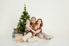 Happy family sitting at the new-year tree on white studio